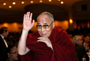 The Dalai Lama waves towards the head table, where U.S. President Barack Obama was seated, during the National Prayer Breakfast in Washington